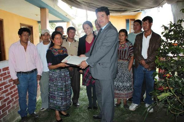Josefina Coyote, presidenta de Asoju, recibe de Ubaldo Villatoro, de Conamigua,  el documento que legaliza la  asociación de  deportados de Patzún.
