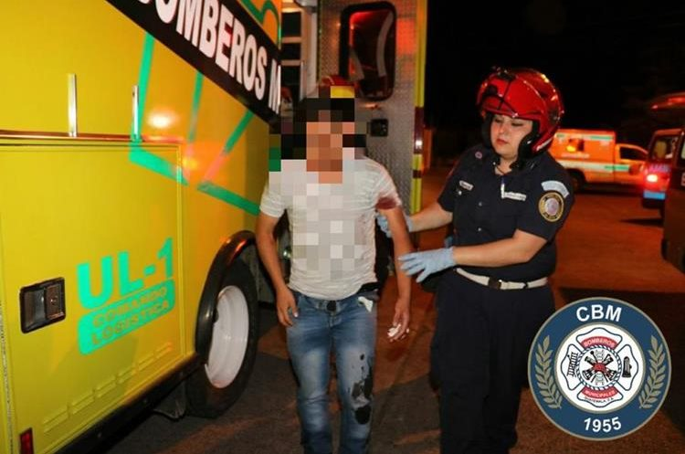 Uno de los heridos en la calzada San Juan es auxiliado por una bombera. (Foto Prensa Libre: Bomberos Municipales).