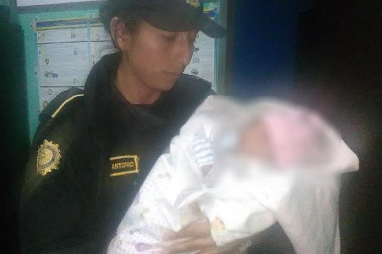 Una agente policial sostiene a la bebé que fue abandonada en un predio de vehículos de Esquipulas, Chiquimula. (Foto Prensa Libre: Mario Morales)