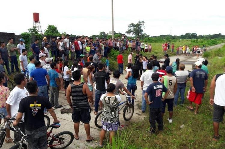 Vecinos llegan a identificar a las víctimas, quienes fueron ultimados en la entrada a la lotificación El Pedregal Cuyotenango, Suchitepéquez. (Foto Prensa Libre: Cristian Soto)