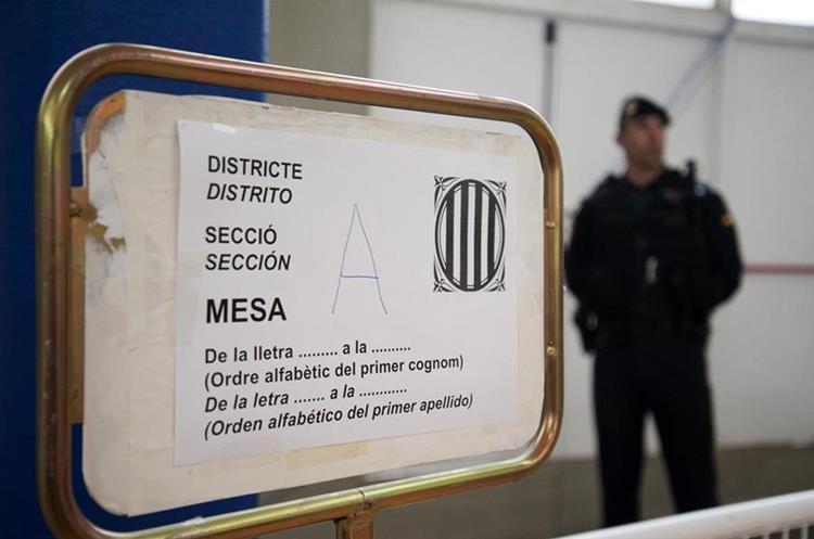 Agentes de la Guardia Civil custodian el colegio de Sant Julià de Ramis (Girona) donde inicialmente tenía previsto votar el presidente de la Generalitat, Carles Puigdemont, en el referéndum independentista del 1-O suspendido por el Tribunal Constitucional. (Foto Prensa Libre: EFE)