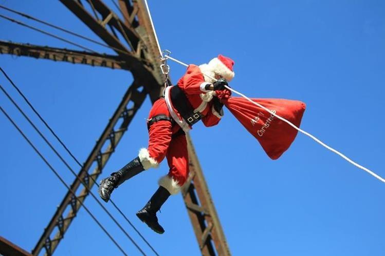 Santa Claus bajó del puente Las Vacas en la zona 5 para dar regalos a niños que viven en asentamientos. (Foto Prensa Libre: Esbin Gacía)