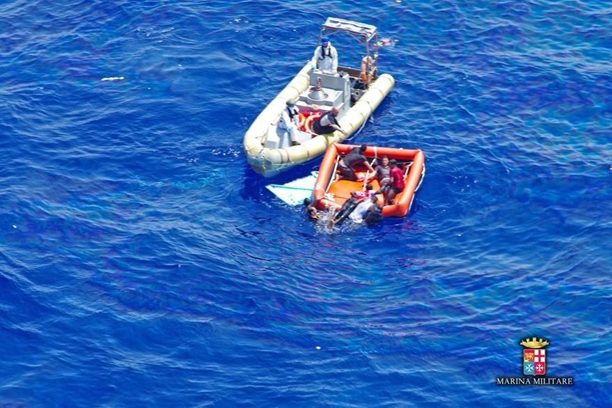 Miembros de la Marina rescatan a inmigrantes en medio del mar, la balsa de indocumentados está a punto de hundirse. (Foto Prensa Libre: AFP).