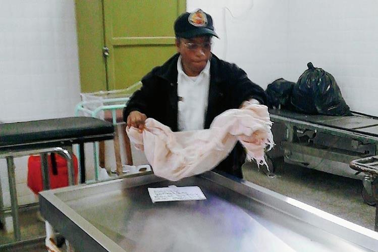 Bomberos ingresan el cuerpo del menor a la morgue del Hospital Nacional de Sololá. (Foto Prensa Libre: Ángel Julajuj)