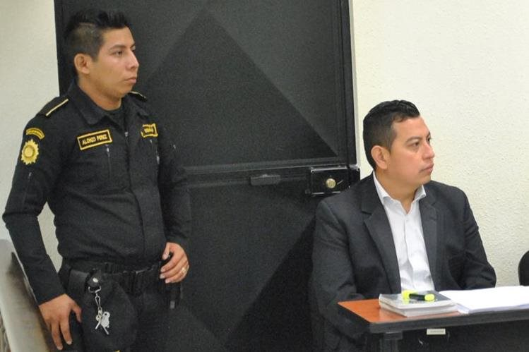 Byron Sales Curiel, el pastor evangélico condenado por defraudación, es custodiado por un policía durante la sentencia. (Foto: Prensa Libre)