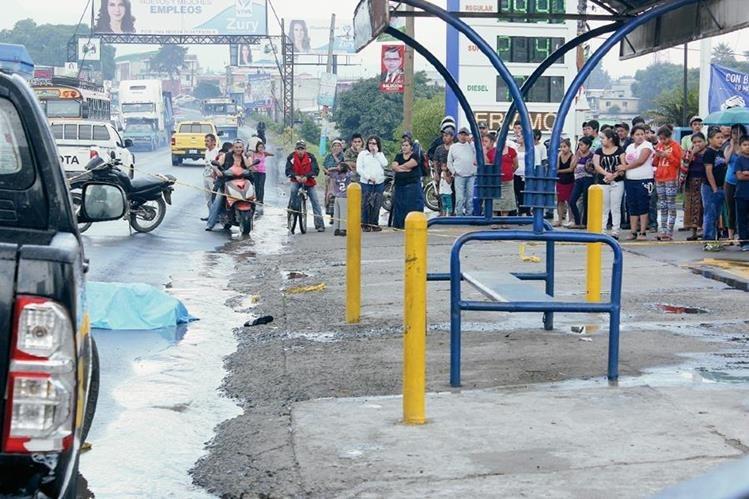 Curiosos observan el cadáver de Gerson David Pineda, quien murió baleado en El Tejar. (Foto Prensa Libre: Víctor Chamalé)