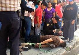 Un agente policial toma datos al hombre que fue atado por la turba. (Foto: Prensa LIbre: @stereo100xela)