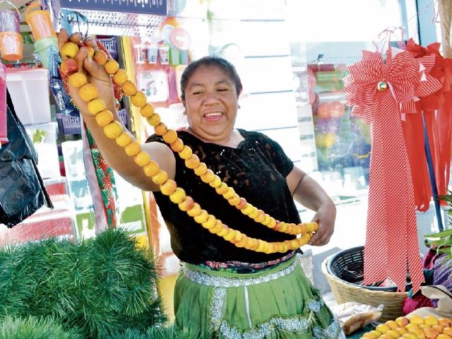 """El olor a la manzanilla identifica las fiestas en Guatemala. """"Vendemos desde hace 15 años manzanilla y  musgo"""", dice Paula Piche,  que desde el 1 de diciembre mantiene una venta con adornos navideños. """"Poco a poco van cambiando las modas, pero las tiras de pino y las patas de gallo siempre están en la tradición"""", comenta."""