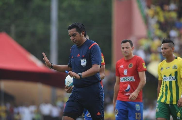 El árbitro Éver López pide tranquilidad a los jugadores.