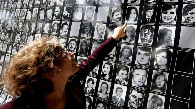 Josefina Giglio señala el retrato de su madre dentro de un cartel en el lugar donde estaba ubicado el centro de tortura El Atlético. EAAF