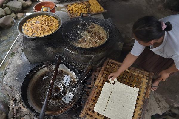 Un trabajador corta la pasta blanca en cuadrados. Así se fabrica el tofu.(AFP).