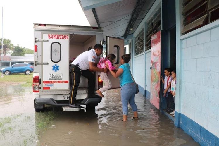Una maestra pone fuera de riesgo a una niña en la escuela de la comunidad Ixlú. (Foto Prensa Libre: Rigoberto Escobar)