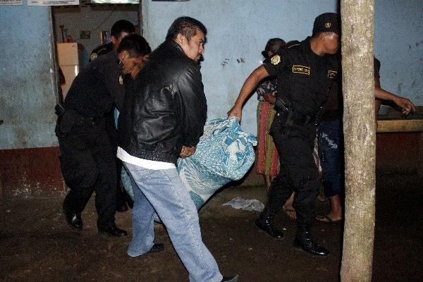 Agentes de la PNC trasladan el cuerpo.