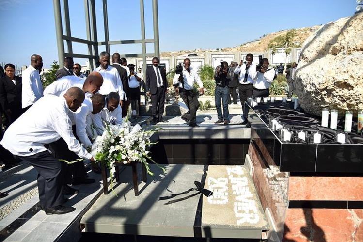 Haitianos colocan flores en recuerdo de las víctimas del terremoto. (Foto Prensa Libre: AFP).