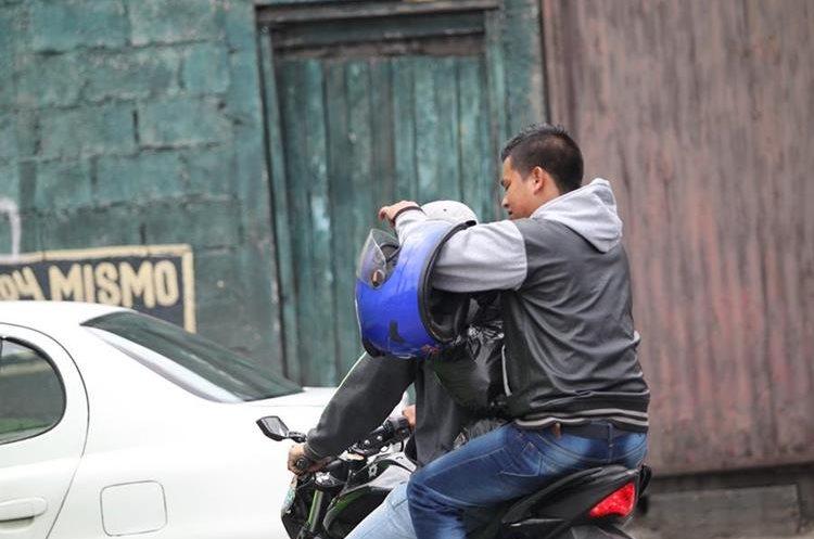 Un motoristas transita por el Centro Histórico con el casco en el brazo. (Foto Prensa Libre: Érick Ávila)