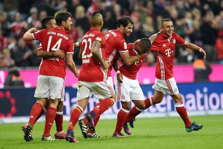 Douglas Costa es felicitado por sus compañeros tras anotar un gol del Bayern.(Foto Prensa Libre: EFE).