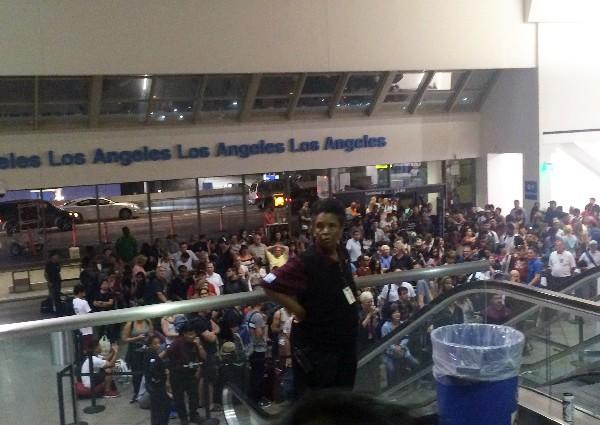 Pasajeros esperan mientras eran reevaluados por la seguridad en el Aeropuerto de Los Ángeles. (AP).