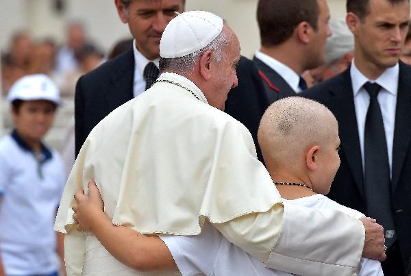 El Papa abraza a un niño durante su audiencia semanal.