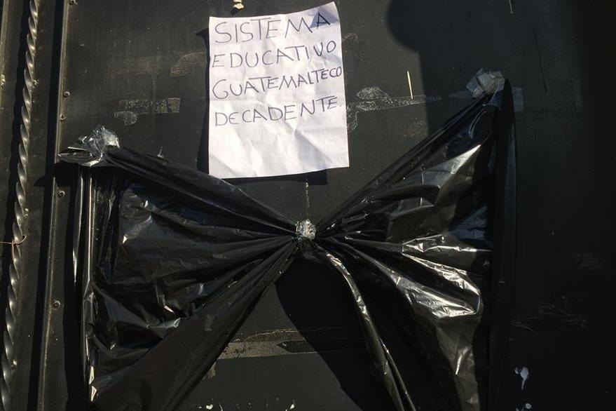 Los manifestantes colocaron una moña negra en una de las puertas de la Dirección Departamental de Educación en Huehuetenango. (Foto Prensa Libre: Mike Castillo)