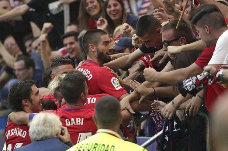 Yannick Carrasco elebra con los aficionados su gol marcado ante el Sevilla. (Foto Prensa Libre: EFE)