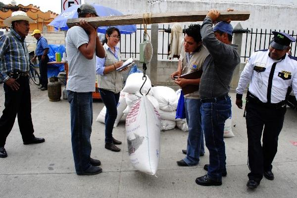 Personal de la Diaco pesa un saco de maíz en  Cubulco, Baja Verapaz.