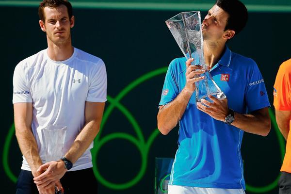 Novak Djokovic besa en trofeo de Miami ante la mirada de Andy Murray. (Foto Prensa Libre: AFP)