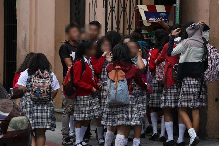 Alumnas del instituto Maria Luisa Samayoa Lanuza, ubicado en la 10a avenida y 9a calle, zona 1, conversan con dos jóvenes con aspecto de pandilleros a la hora de salida. (Foto Prensa Libre: Paulo Raquec)