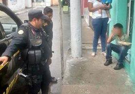 Policías hacen preguntas al niño que, sentado, trata de buscar consuelo por la pérdida del producto luego de que fue asaltado. (Foto Prensa Libre: Cortesía)