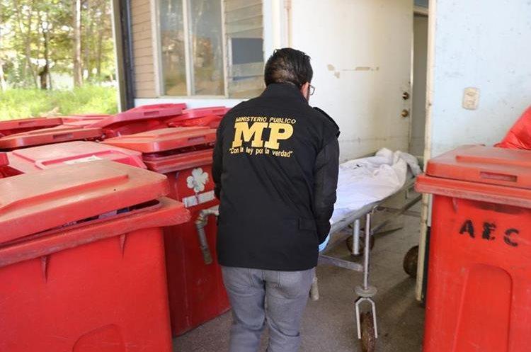 Un fiscal del Ministerio Público ingresa el cadáver de la mujer a la morgue del Instituto Nacional de Ciencias Forenses en San Marcos. (Foto Prensa Libre: Whitmer Barrera)