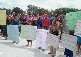 Pobladores de  la Reserva de Biósfera Maya, que se oponen a los desalojos, portaban pancartas. (Foto Prensa Libre: Rigoberto Escobar)