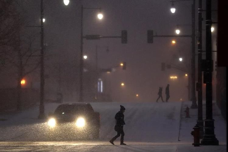 Peatones pasan a través de una calle nevosa en el centro de Kansas City, Missouri. (Foto Prensa Libre: AP).