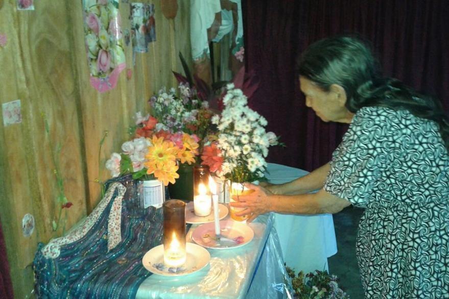 María Antonia Paz adorna una pared donde asegura que hay una imagen religiosa. (Foto Prensa Libre: Walfredo Obando)