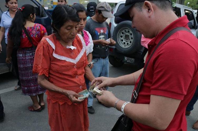 Una mujer cambia lempiras a quetzales en la frontera de Corinto, entre Honduras y Guatemala, luego de que   fueron víctimas de explotación laboral. (Foto Prensa Libre: Dony Stewart)