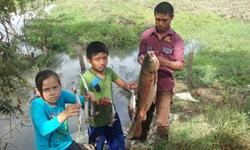 Niños muestran algunos de los peces muertos encontrados en el arroyo San Ramón, Sayaxché, Petén. (Foto Prensa Libre: Rigoberto Escobar)