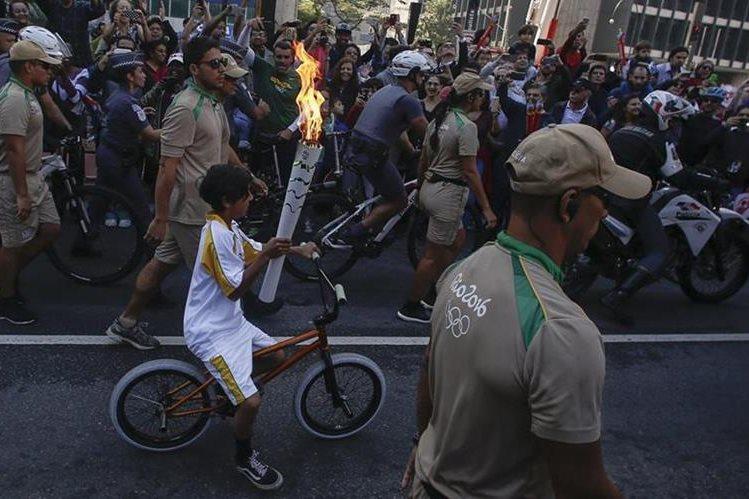 Un niño residente de Sao Paulo porta la llama olímpica. (Foto Prensa Libre: AFP)