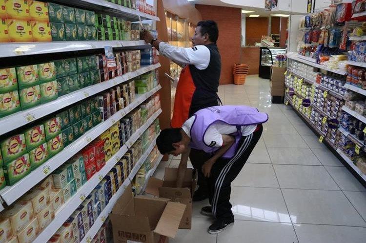 Víctor Ixcot recibe ayuda de un compañero para ordenar. (Foto Prensa Libre: María José Longo)