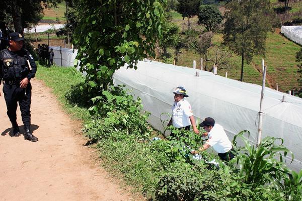 Socorristas observan el cuerpo sin vida de un hombre, en Sumpango, Sacatepéquez. (Foto Prensa Libre: Renato Melgar)