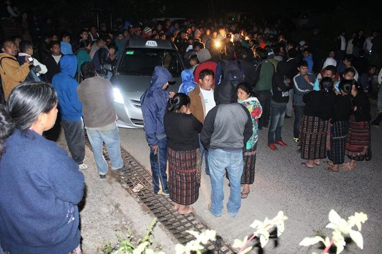 Vecinos de la cabecera de Sololá observan escena del crimen donde murió el piloto de taxi Alexánder Xep Chumil. (Foto Prensa Libre: Ángel Julajuj)
