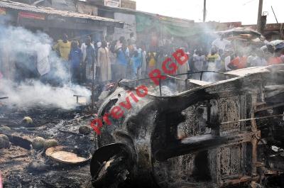 Varias personas observan un vehículo destruido por una bomba. (Foto Prensa Libre:AFP).