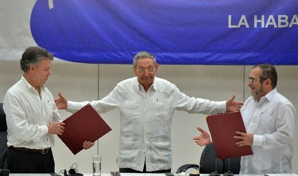 """Juan Manuel Santos (i) y Timoleón Jiménez, alias """"Timochenko"""" (d),y Raúl Castro (c) durante la firma del alto el fuego. (AFP)."""