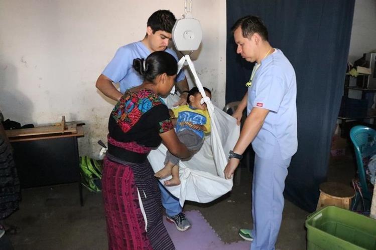 Dos médicos del programa Pop Wuj ayudan a una mujer a pesar a su hijo. (Foto Prensa Libre: María José Longo)