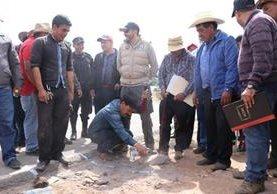 El alcalde auxiliar de la aldea Tuichán, Ixchiguán, Gilberto Chávez, se sostiene de su vara edil mientras marca en el suelo una línea divisoria. (Foto Prensa Libre: Whitmer Barrera)