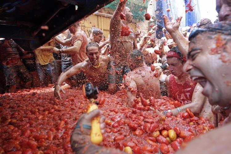 Participantes se lanzan tomates en la tradicional fiesta de Buñol, Valencia. (Foto Prensa Libre: AP).