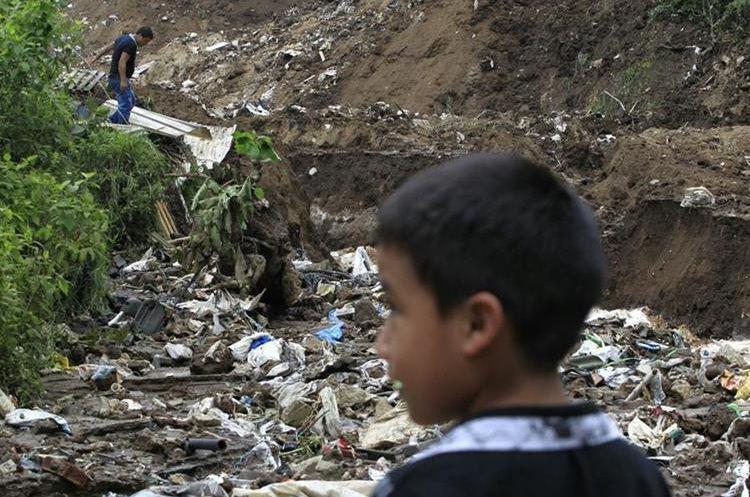 Niño observa la casa destruida de sus vecinos. Su vivienda está a cinco metros del lugar del derrumbe. (Foto Prensa Libre: Carlos Hernández)