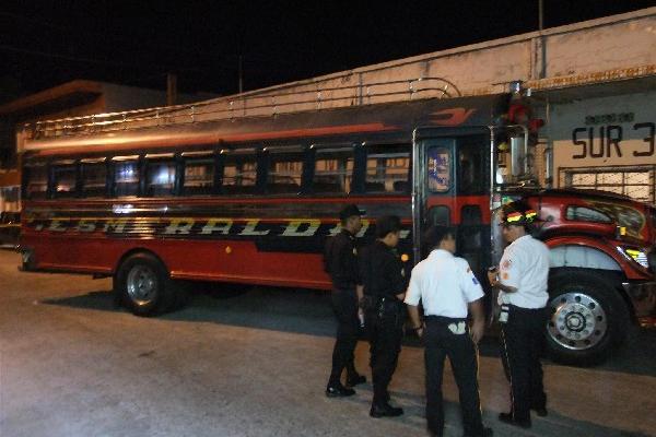 Agentes examinan   el autobús asaltado.