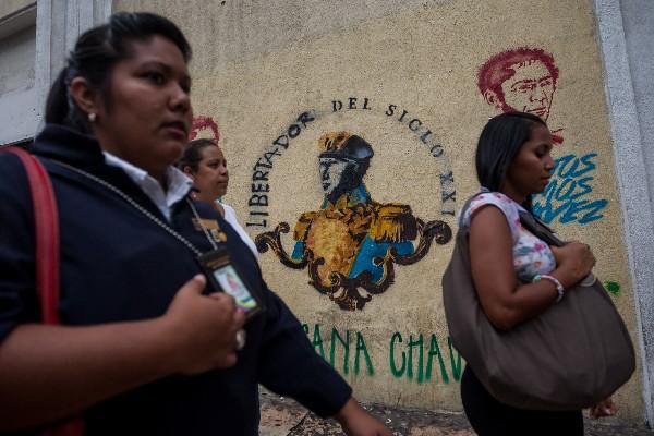 Venezolanos caminan frente a un grafiti del fallecido presidente Hugo Chavez.