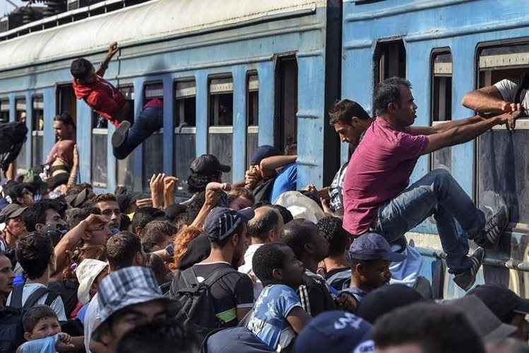 Varios inmigrantes tratan de subirse a uno de los vagones de un tren con destino a Serbia en la estación de Gevgelija, Macedonia. (Foto Prensa Libre: EFE).