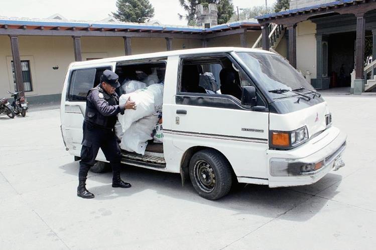 Agente de la PNC saca del microbús parte de la mercadería robada en San Martín Jilotepeque. (Foto Prensa Libre: Víctor Chamalé)
