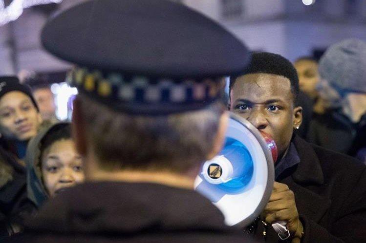 Descontentos gritan consignas a un policía en Chicago. (Foto Prensa Libre: AFP)