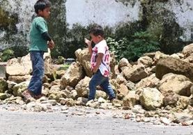 Dos niños caminan frente a los escombros de la iglesia de Samayac, la cual, en parte, cedió a la fuerza del sismo. (Foto Prensa Libre: Cristian Icó)
